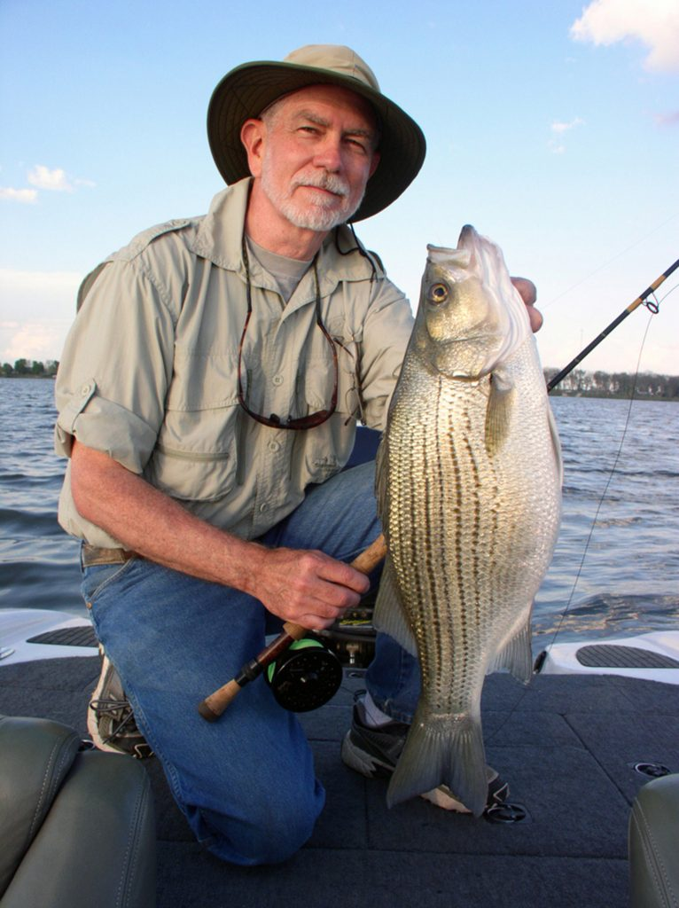 Fisherman in a boat holding up a hybrid striped bass