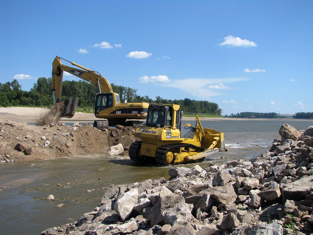 Heavy construction equipment digging out dirt from a channel of the Mississippi River