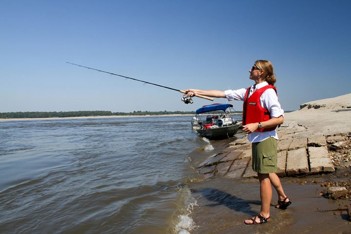 Woman with life vest on casting her line from a fishing pole on the shores of the Mississippi River
