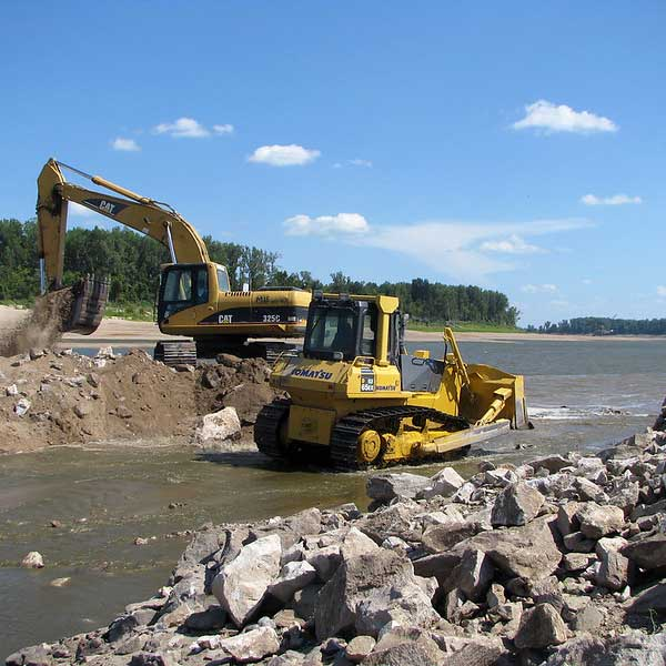 Heavy construction equipment digging out dirt from a river channel with rocks in the foreground